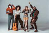 Fotografia multiculturale retrò in stile amici divertendosi con la chitarra ed elettronica vintage su grey