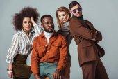 Fotografia multiculturale retrò in stile amici in posa isolato su grigio