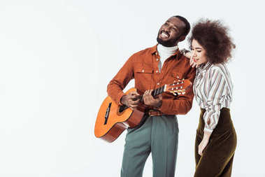 happy african american guitarist playing for girlfriend isolated on white