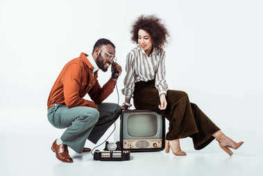 african american retro styled couple with vintage television and phone on white