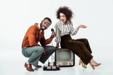Happy african american retro styled couple with vintage television and phone on white stock vector