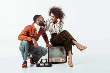 african american retro styled girlfriend sitting on vintage television and and talking by phone on white