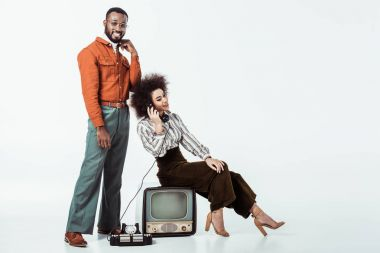 happy african american retro styled girlfriend sitting on vintage television and and talking by phone on white