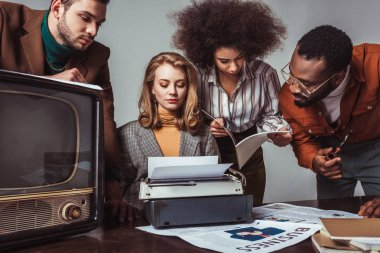 multicultural retro styled friends working in newsroom isolated on grey