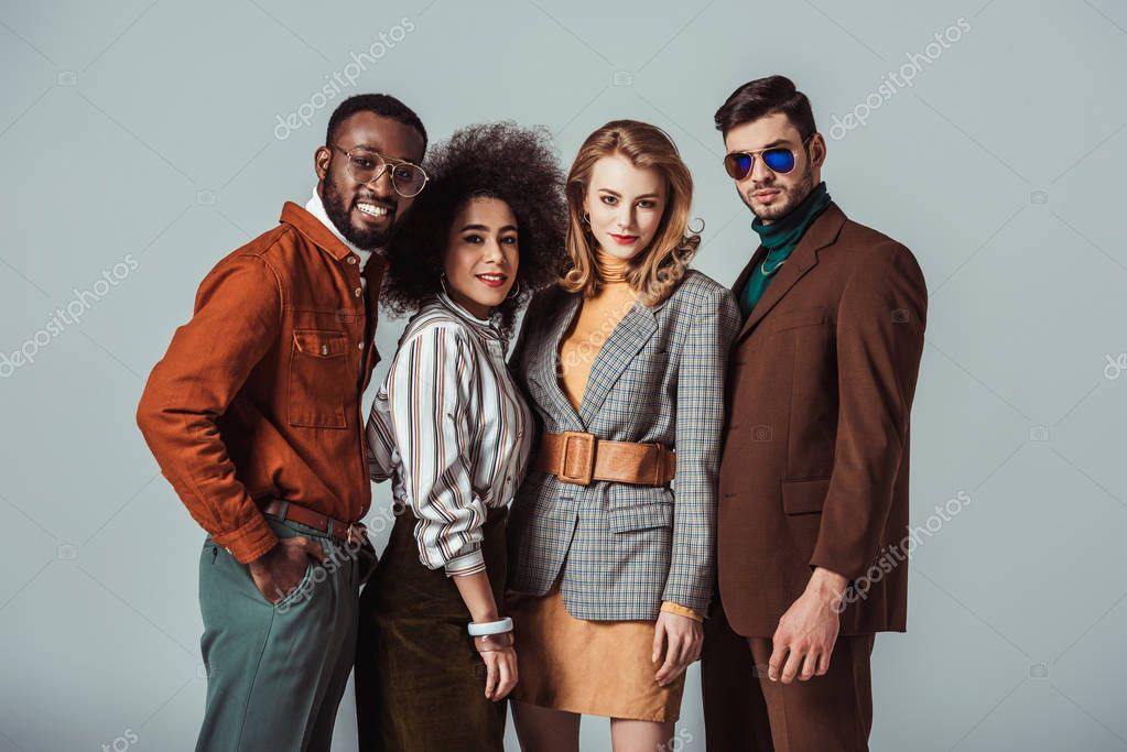 happy multicultural retro styled friends standing at looking at camera isolated on grey