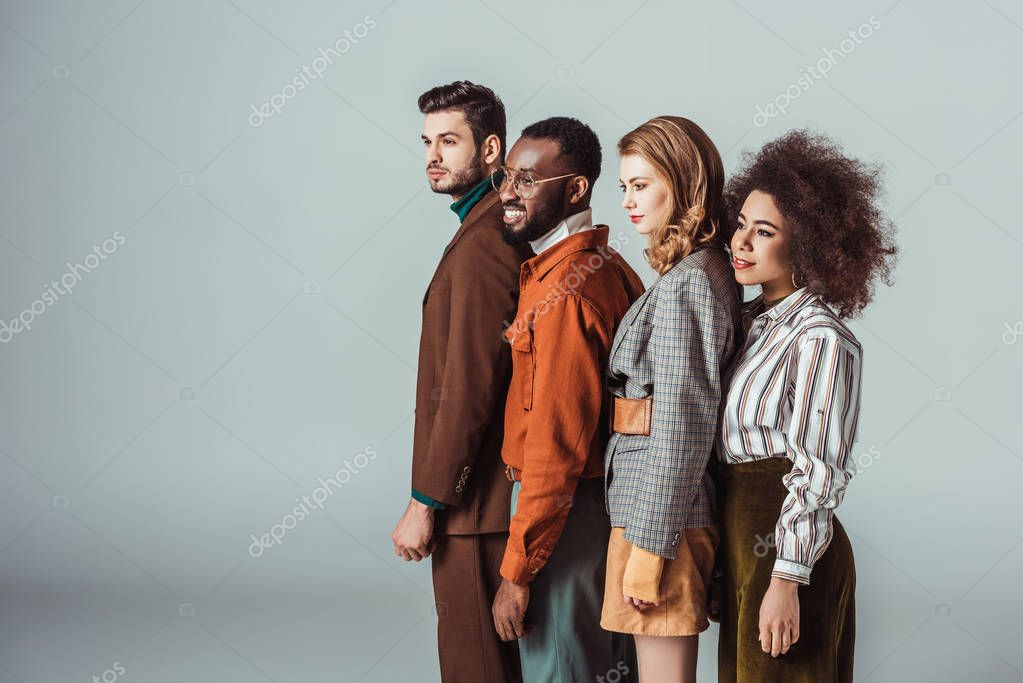 side view of smiling multicultural retro styled friends looking away isolated on grey