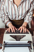 Fotografie cropped image of retro styled african american journalist typing at typewriter