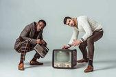 multikulturális retro stílusú meg guggolva vintage rádió és a televízió, a szürke
