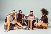 multikulturní retro stylu Přátelé sedící u stolu, dívka ladění vintage rádio