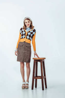 beautiful retro styled girl standing near wooden chair on white
