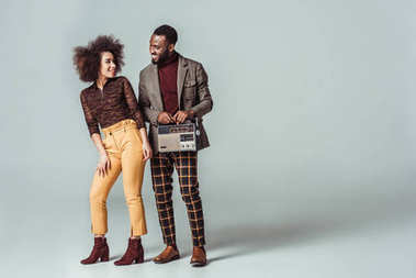 happy african american retro styled couple looking at each other with vintage radio on grey