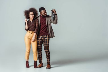 happy african american retro styled couple with vintage radio on grey