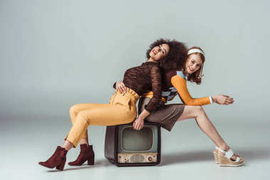 happy multicultural retro styled girls posing on vintage television on grey