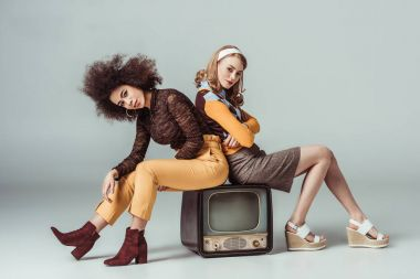 multicultural retro styled girls sitting on vintage television and looking at camera on grey
