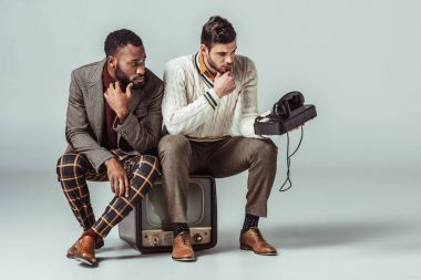 multicultural retro styled friends sitting on vintage television and looking at stationary telephone