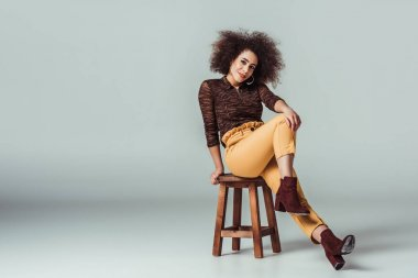 smiling african american woman in retro clothes posing on chair on grey