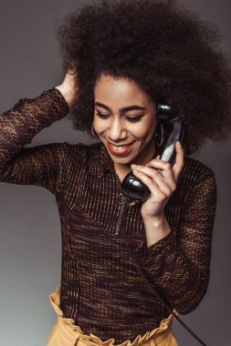 smiling african american retro styled girl talking by vintage stationary telephone isolated on grey