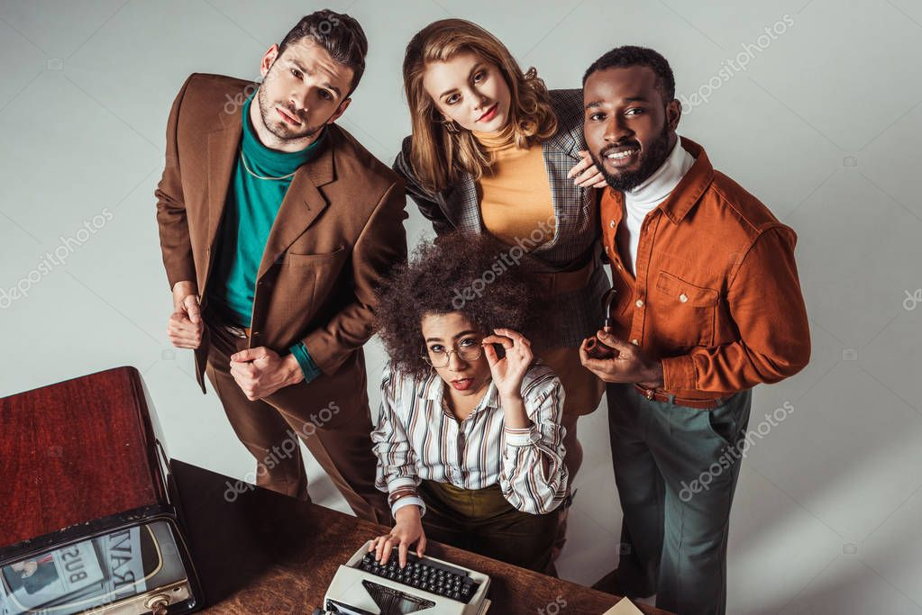 overhead view of multicultural retro styled friends with typewriter looking at camera