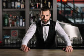 Fotografie handsome bartender leaning on bar counter and looking at camera