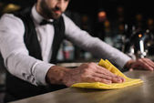 Photo cropped image of bartender cleaning bar counter in evening