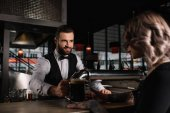 Photo smiling handsome bartender giving glass of beer to female visitor