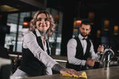smiling bartender cleaning bar counter and looking away