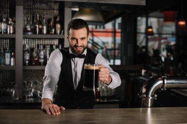 smiling handsome bartender holding glass of beer