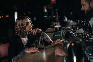 girl drinking beer at bar counter and looking at bartender
