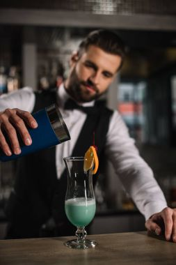 handsome bartender preparing alcohol cocktail