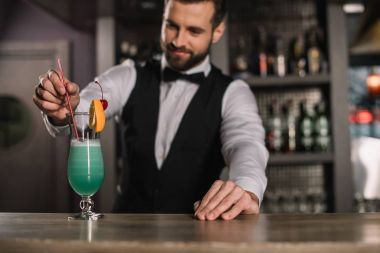 Smiling bartender adding plastic straw to cocktail stock vector