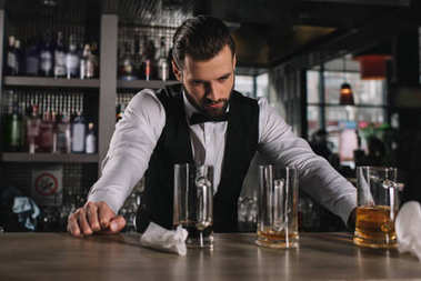 tired handsome bartender leaning on bar counter and looking at dirty glasses and trash