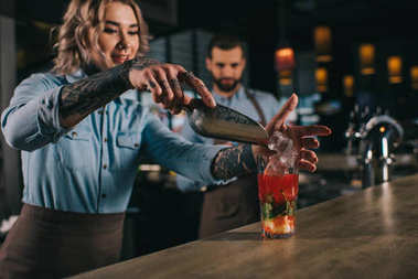 bartender adding ice into alcohol drink at bar