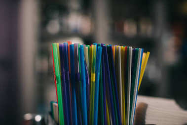 colored plastic straws for drinking on blurred background