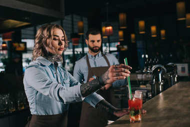tattooed bartender putting plastic straws in glass with alcohol drink at bar