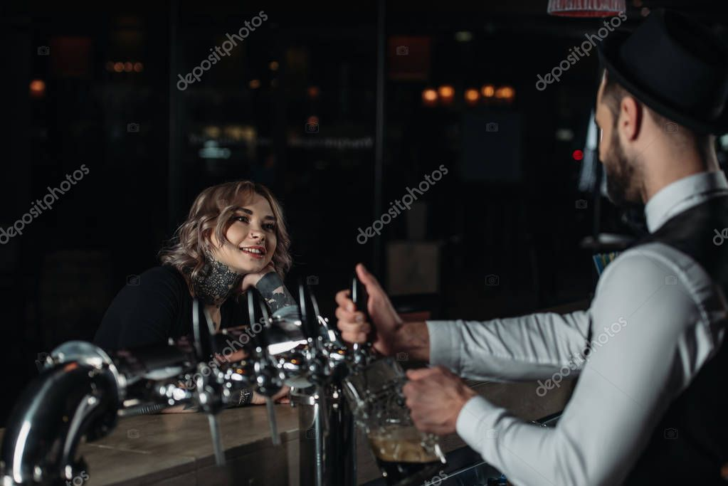 bartender pouring beer from beer taps into glass and looking at female visitor