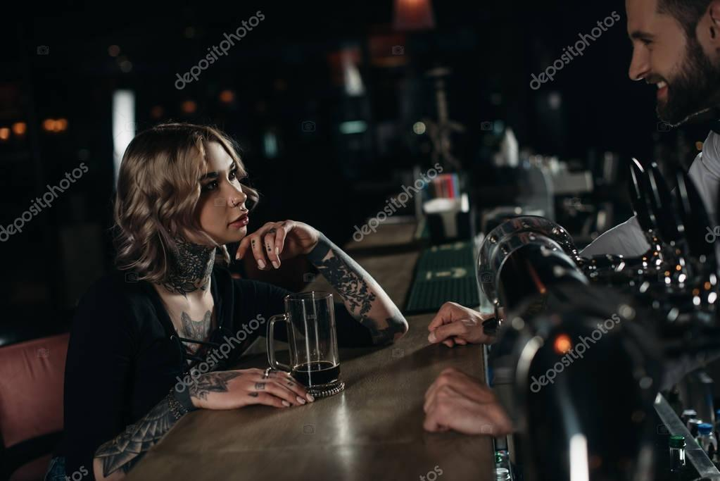 girl drinking beer at bar counter and looking at bartender