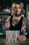 Fotografie Tetovaný barman při pohledu na brýle shot nápoje