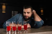 handsome visitor leaning on bar counter and looking at four shot drinks