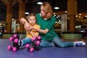 Mutter Aufmunterung verletzten Tochter auf der Rollschuhbahn