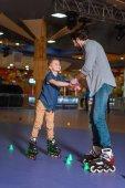 padre e figlio insieme pattinare sulla pista di pattinaggio con i coni
