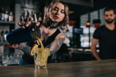 tattooed bartender preparing drink at bar