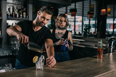 young bartenders preparing alcohol drinks at bar counter