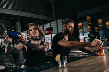 young bartenders preparing alcohol drinks at bar