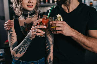cropped image of bartenders clinking with drinks at bar