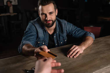 cropped image of visitor sitting at bar counter and giving credit card to bartender