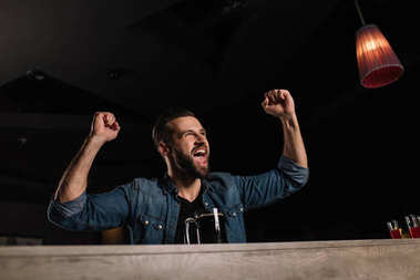 Visitor screaming at bar counter and showing yes gesture while watching football match