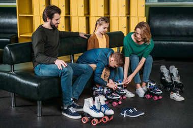 family wearing roller skates before skating in skate park