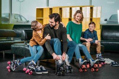 family resting on sofa before skating in roller skates in skate park