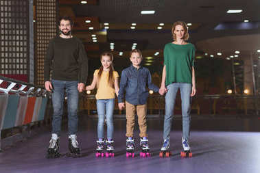 happy family holding hands while skating together on roller rink