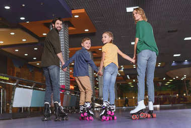 back view of family holding hands while skating on roller rink together